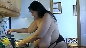 Granny with Giant saggy udders cooks in topless. Massive hang Cow Udders